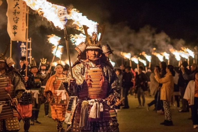 Locals dressed in samurai armor parade through Unzen while carrying torches duri...