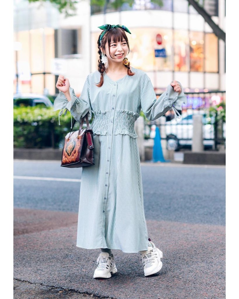 Horie on the street in Harajuku wearing a vintage inspired look featuring a stri...