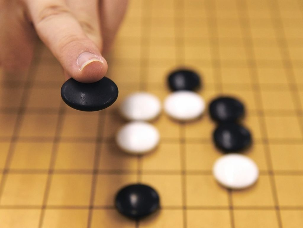 Go is a board game that involves two players, one playing black and one playing ...