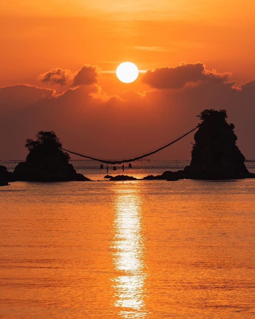 Golden light over Meoto Iwa, the famous wedded rocks of Japan.   These two sacr...